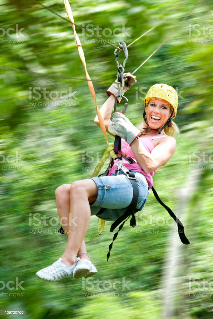 Excited woman on zipline in jungle motion blur stock photo