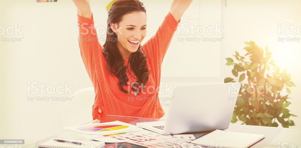 Excited woman raising her arms while working on her laptop stock photo