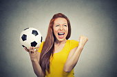 excited woman screaming celebrating team success holding football