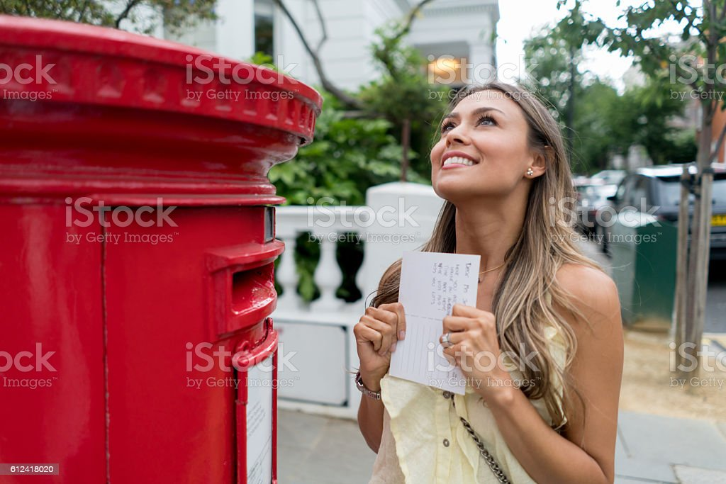Excited woman sending a postcard stock photo