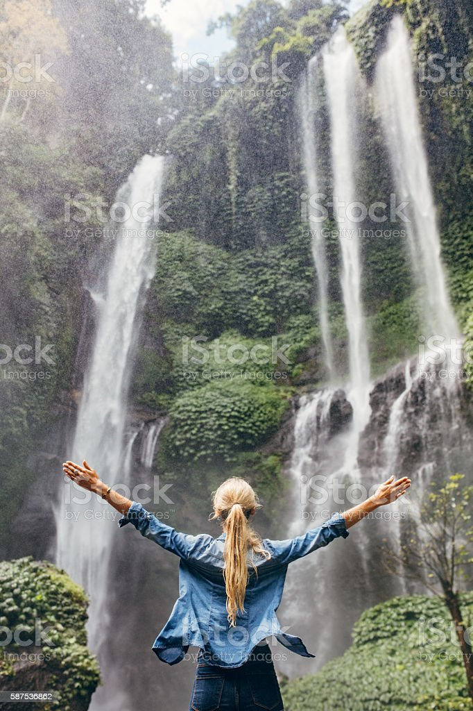 Excited woman standing by waterfall stock photo