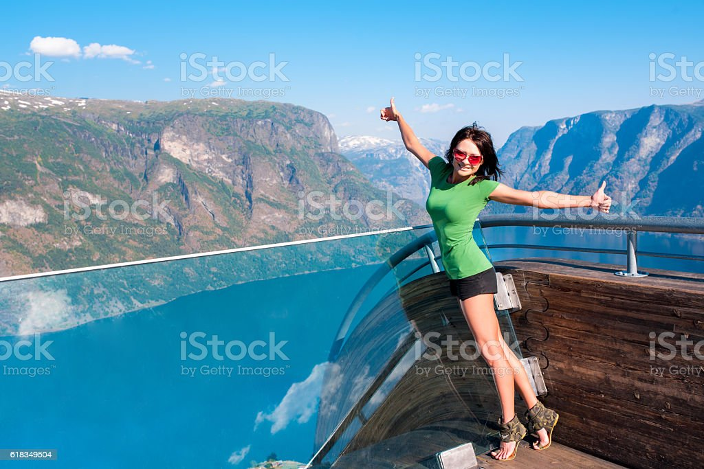 Excited woman tourist at Stegastein Viewpoint stock photo