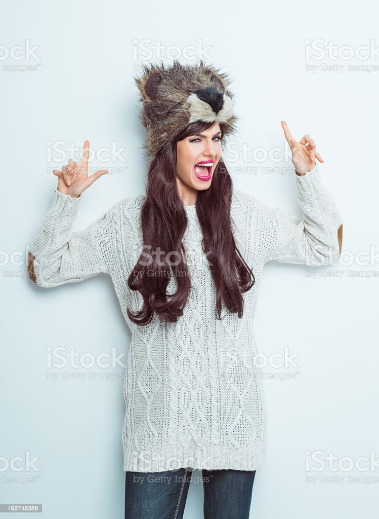 Excited woman wearing bear head fur cap and winter clothes stock photo