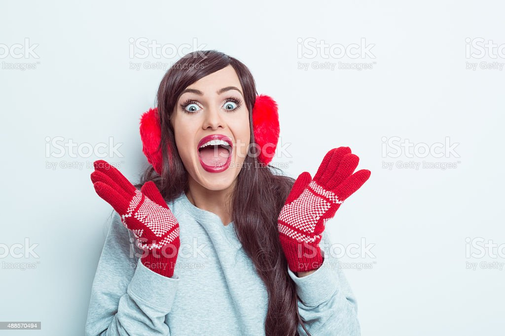 Excited woman wearing red earmuffs and gloves stock photo