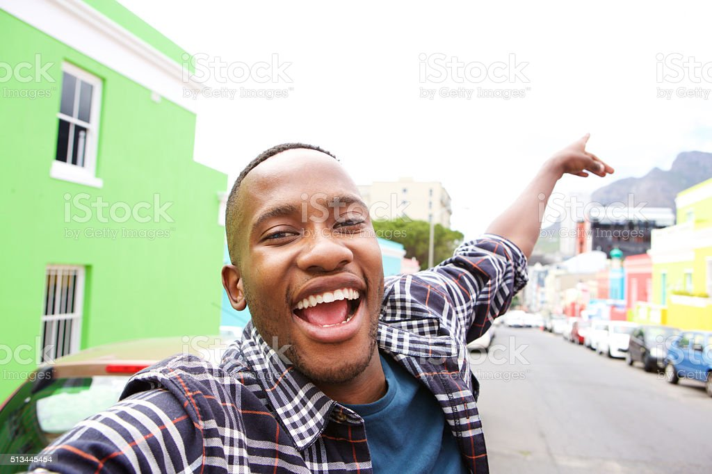 Excited young african guy taking a selfie stock photo