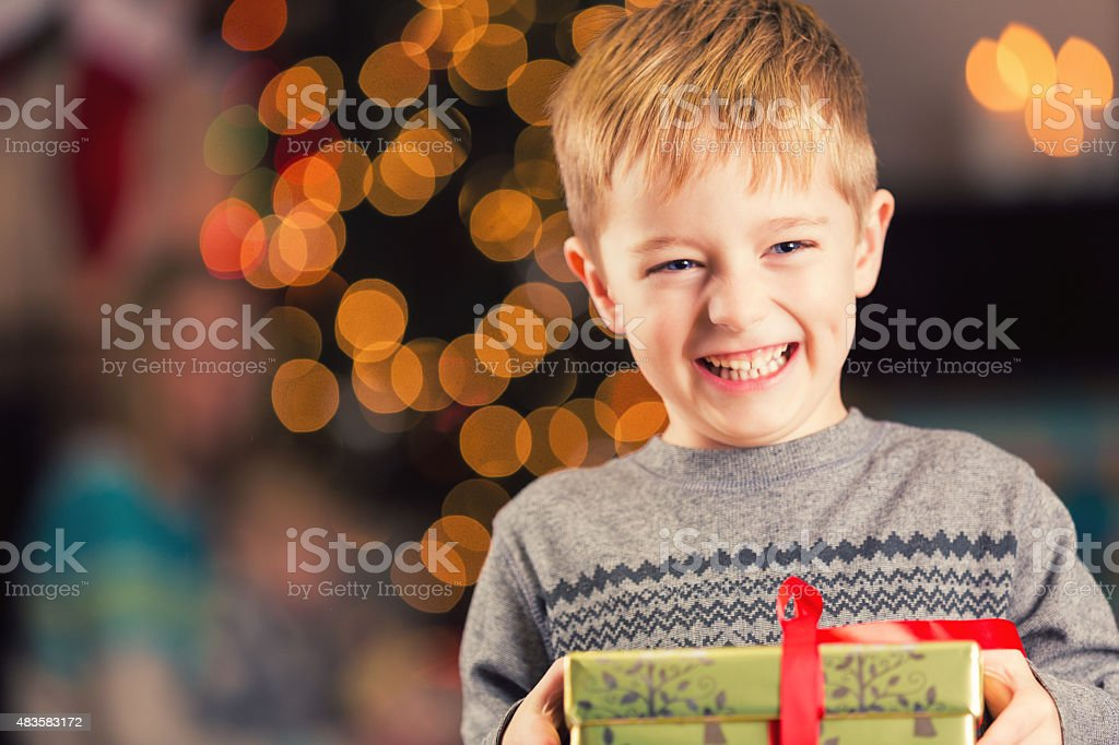 Excited young boy holding Christmas gift in front of tree stock photo