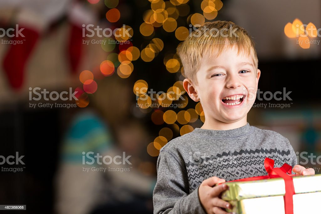 Excited young boy holding present on Christmas day stock photo