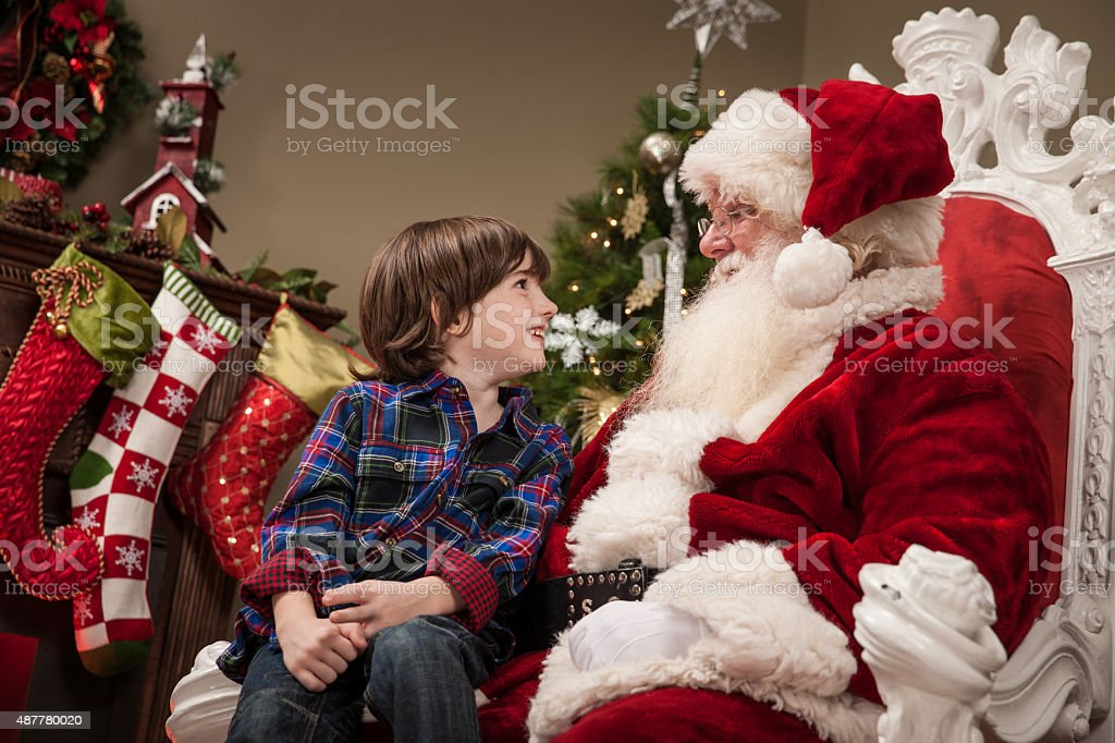 Excited Young Boy Sits on Santa's Lap stock photo