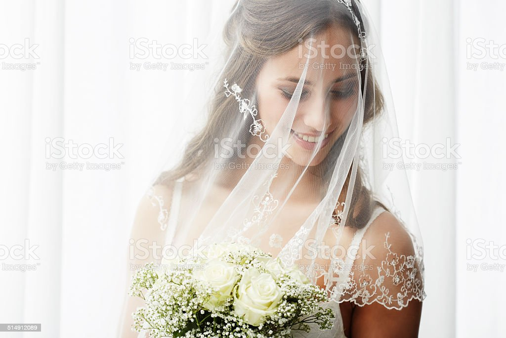 Excited young bride in veil holding bouquet stock photo