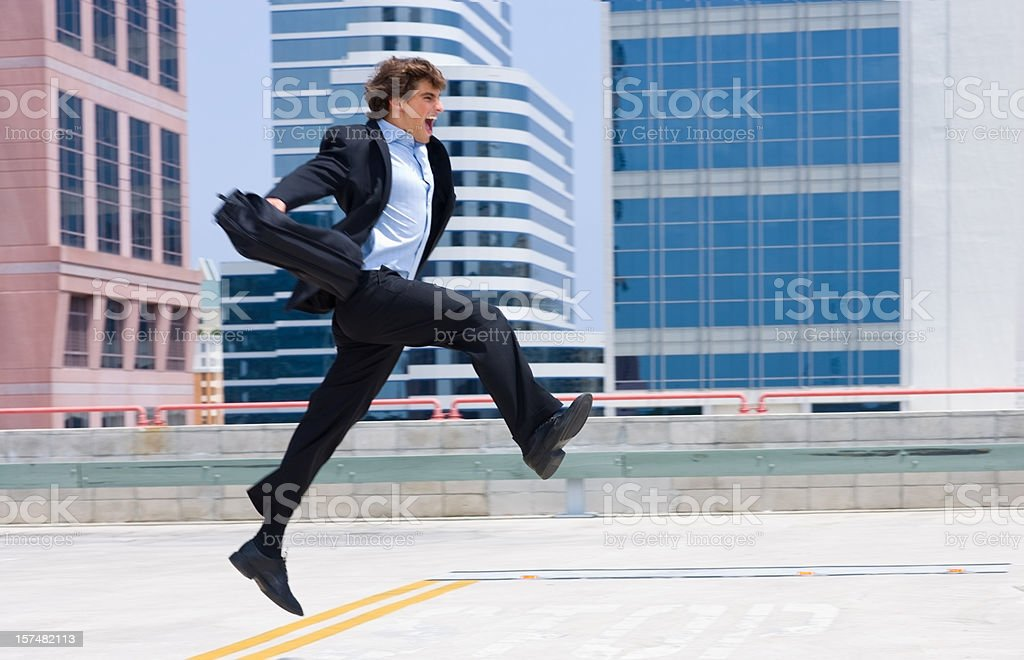 Excited young businessman leaping up with buildings in background royalty-free stock photo