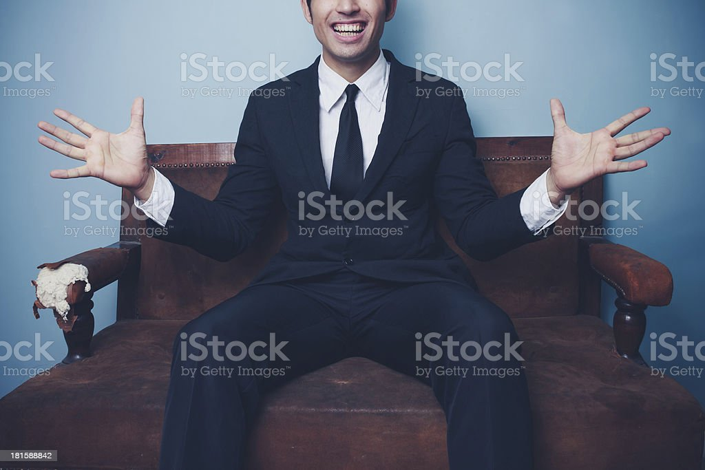 Excited young businessman on sofa royalty-free stock photo