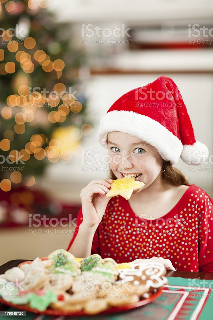 Excited Young Girl Eating Christmas Cookies  in Front of Tree royalty-free stock photo