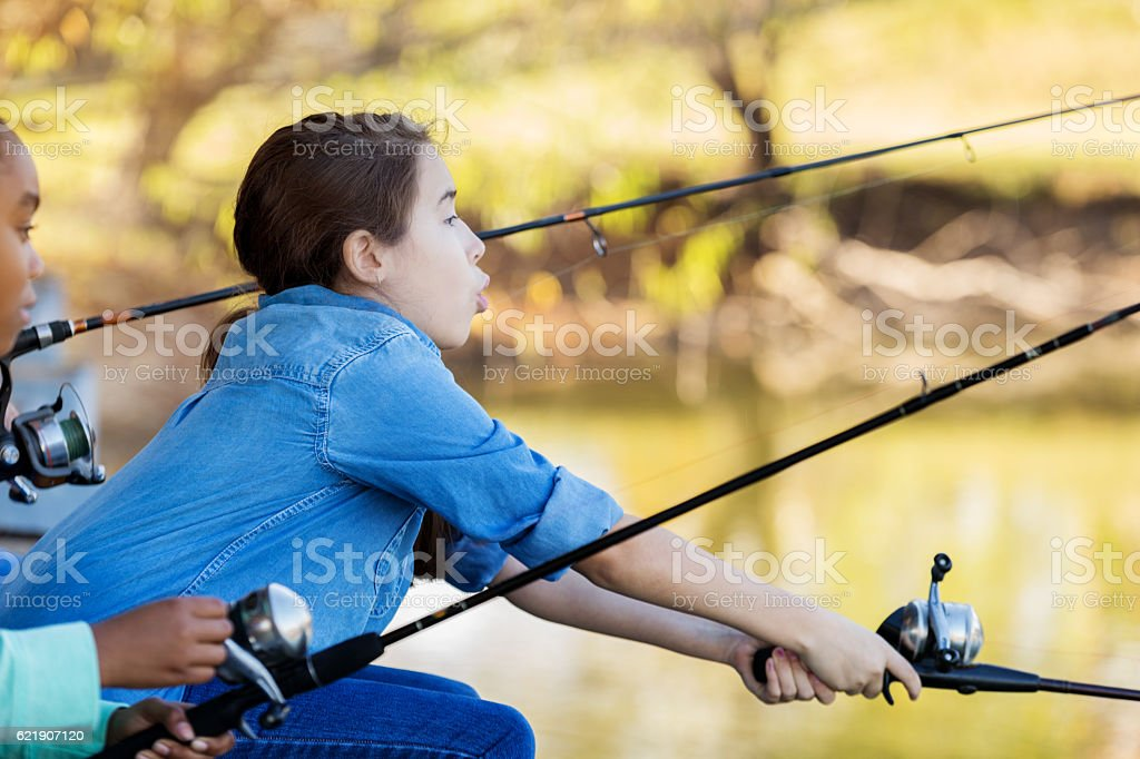 Excited young girl fishes in a local pond stock photo