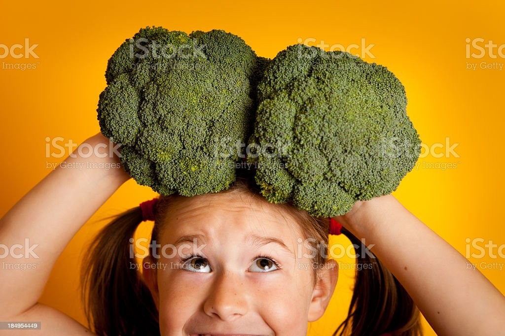 Excited Young Girl Holding Broccoli on Her Head royalty-free stock photo
