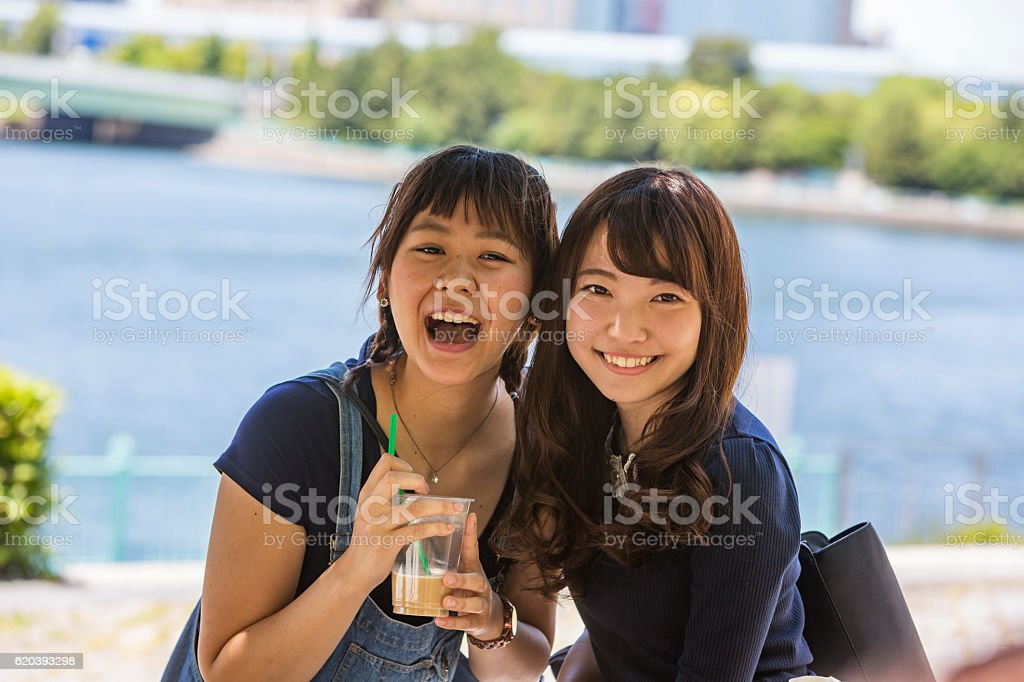 Excited Young Japanese Women Friends Enjoying a Drink stock photo