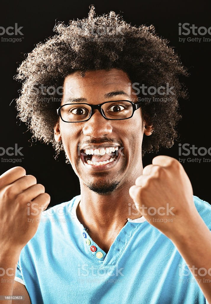 Excited young man smiles and cheers with fists clenched royalty-free stock photo