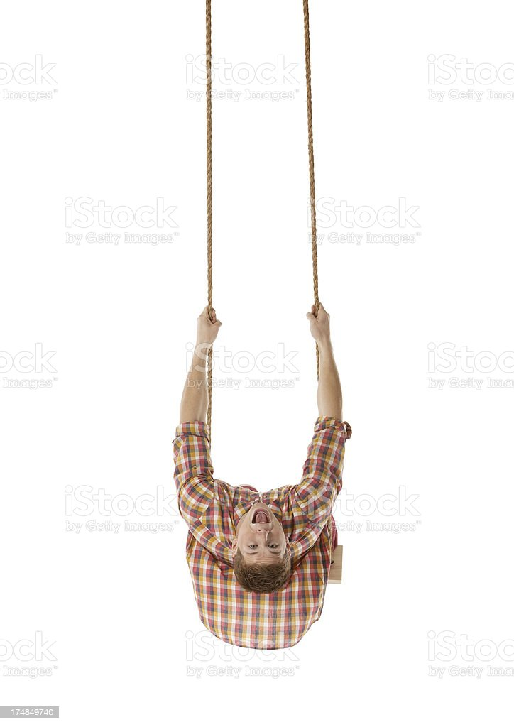 Excited young man swinging on a swing royalty-free stock photo