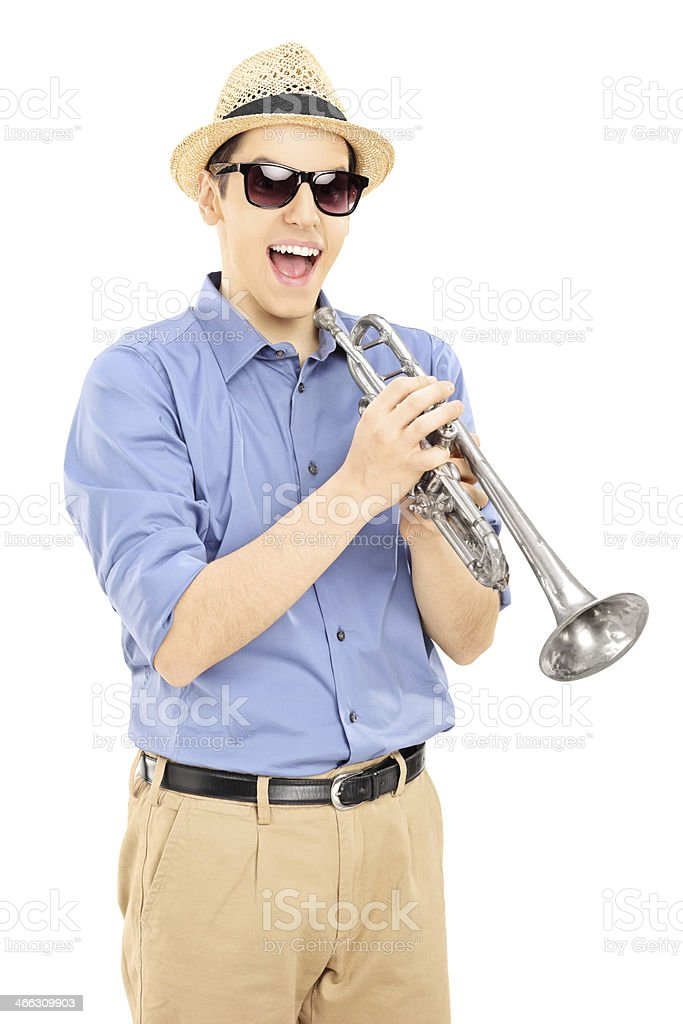Excited young musician wearing sunglasses and holding a trumpet royalty-free stock photo