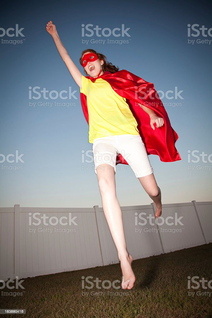 Excited Young Superhero Jumping Up to the Sky royalty-free stock photo