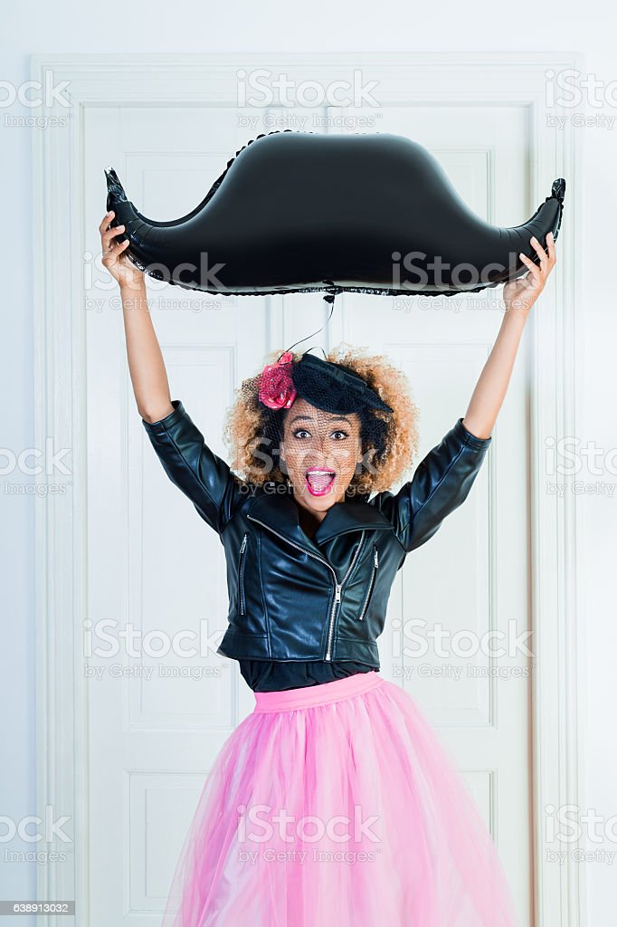 Excited young woman holding mustache balloon indoors stock photo