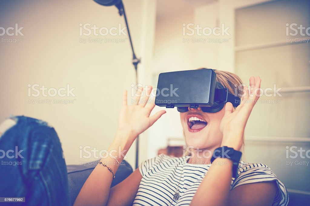 Excited young woman using virtual reality headset at home stock photo