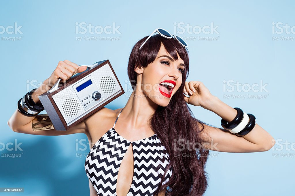 Excited young woman wearing swimsuit, listening to the radio stock photo