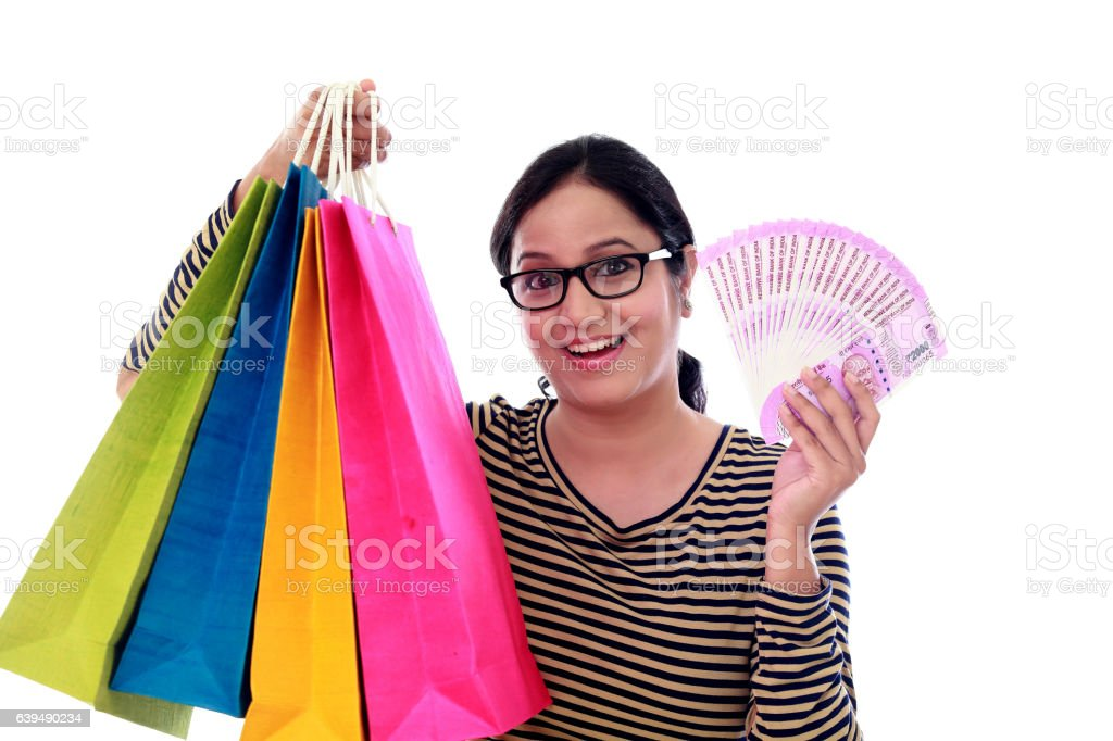 Excited young woman with shopping bags and 2000 rupee notes stock photo