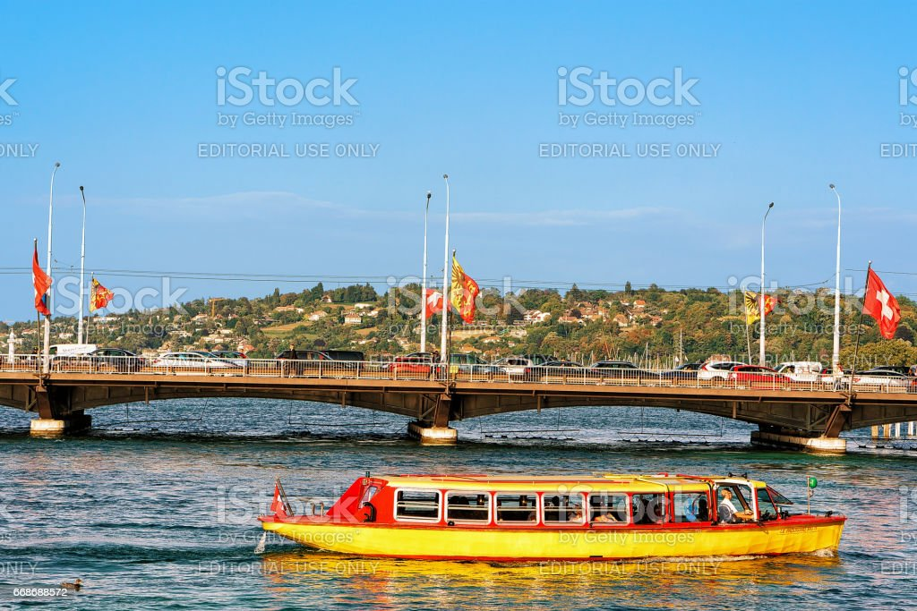 Excursion ferry at Geneva Lake and Bergues bridge flags Swiss stock photo