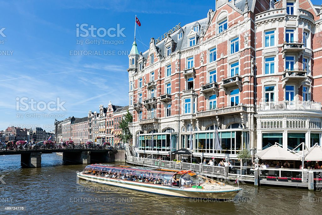 Excursion ship with tourists in Amsterdam canal stock photo
