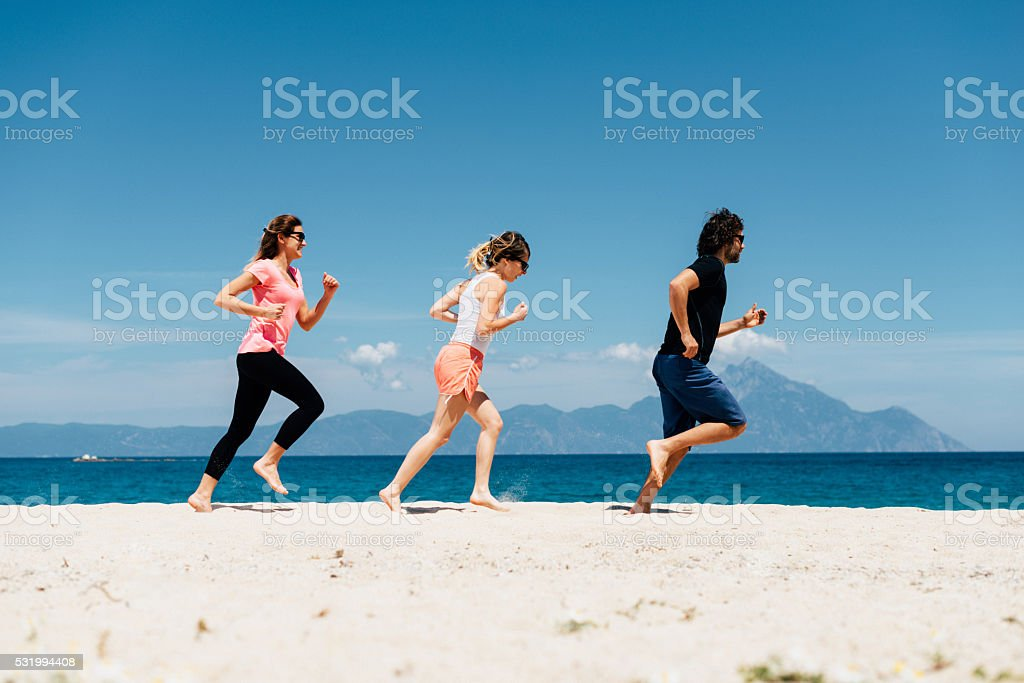 Execising in team and having fun together on summer holiday stock photo