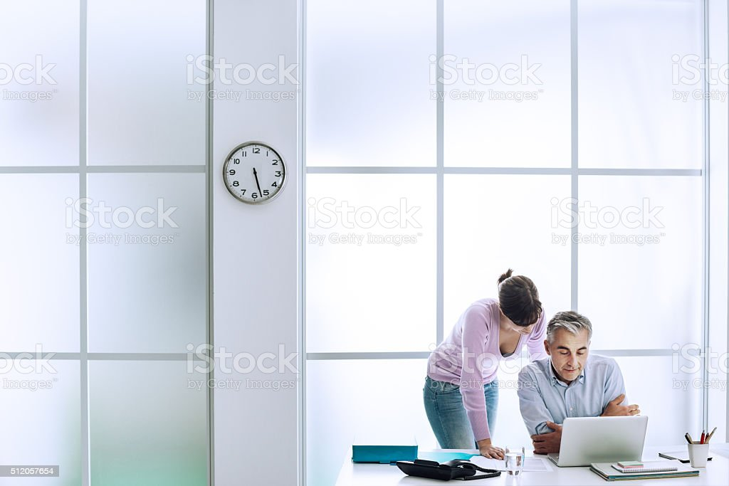 Executive at work with his assistant stock photo