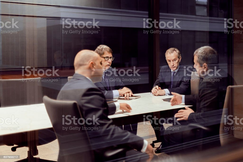 Executive businessmen talking in meeting room stock photo