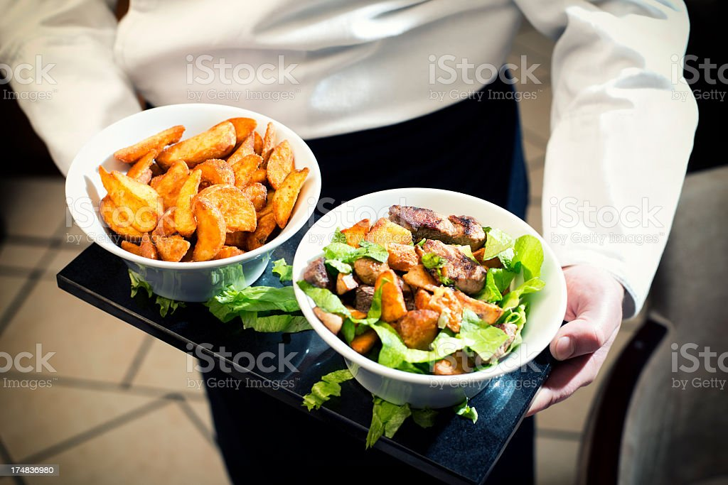 Executive chef serving salad and home fries stock photo