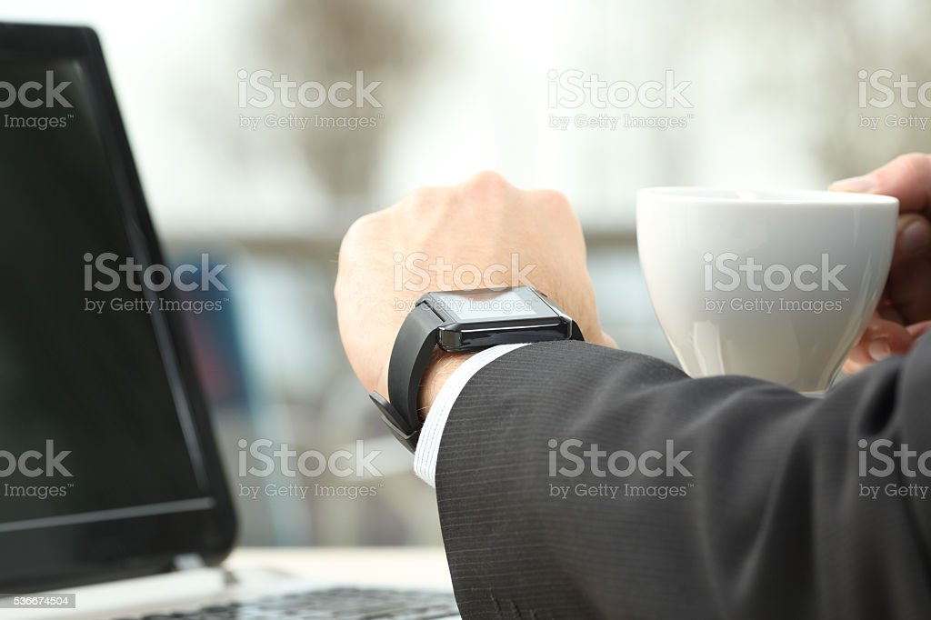 Executive consulting a smart watch in a bar stock photo