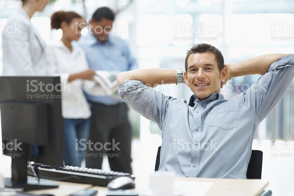 Executive relaxing at desk with colleagues in the background royalty-free stock photo