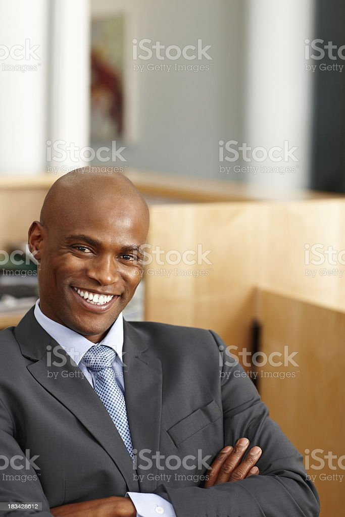 Executive smiling while sitting at desk royalty-free stock photo