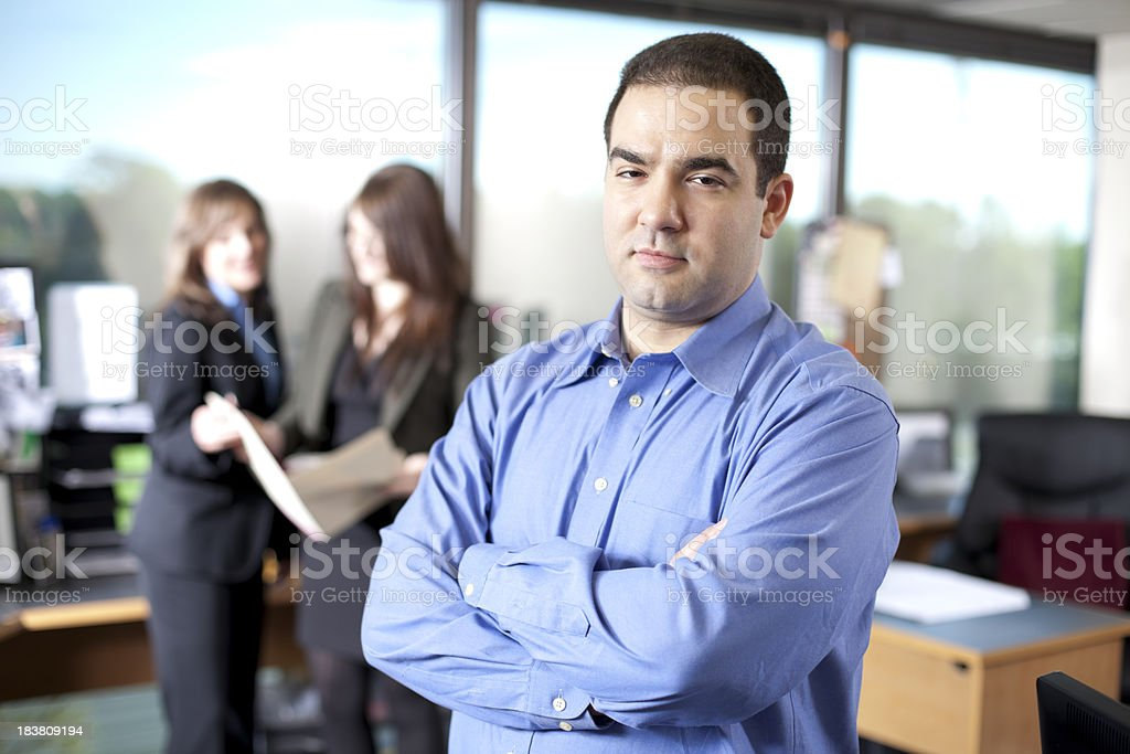 Executive with folded arms and colleagues in background royalty-free stock photo