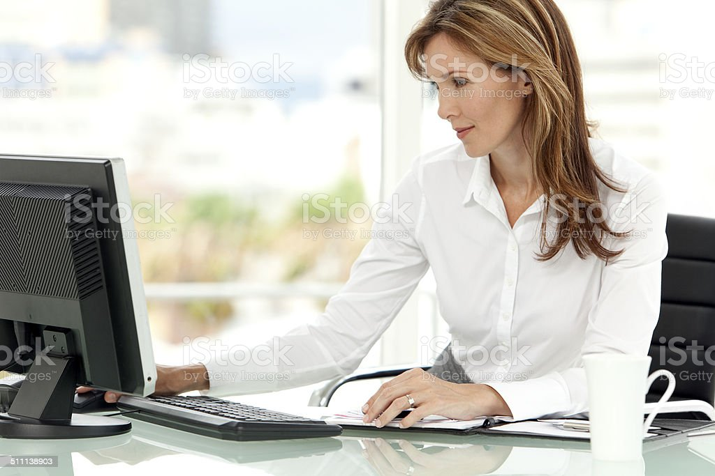 Woman using computer at workplace stock photo