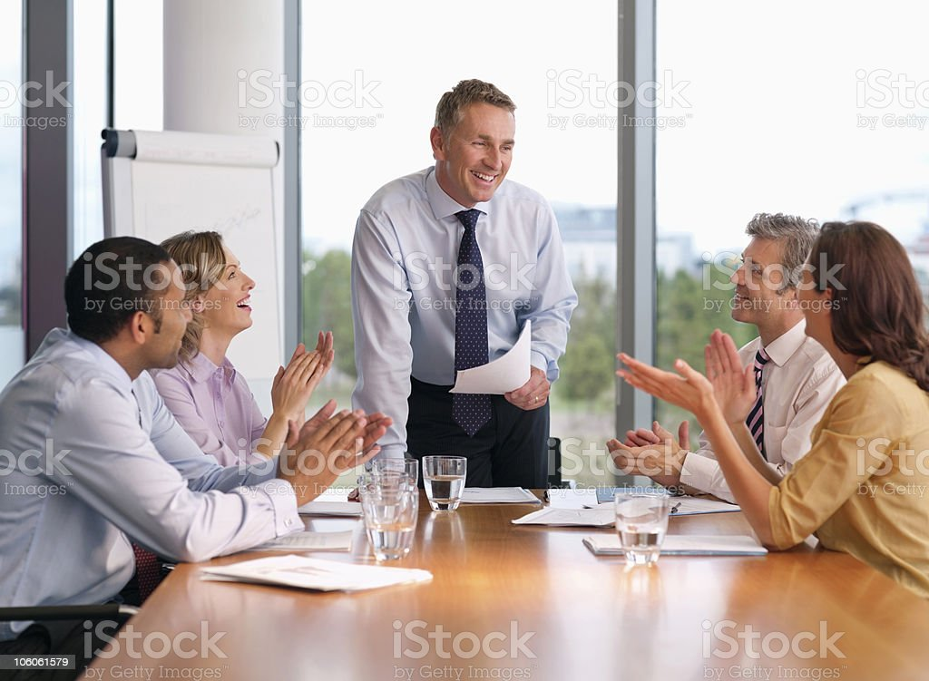 Executives applauding their colleague during a presentation royalty-free stock photo