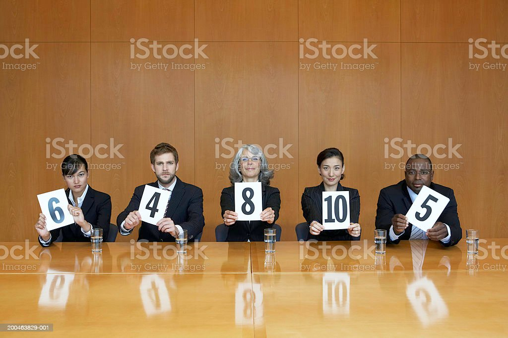 Executives at conference table holding score cards, portrait stock photo