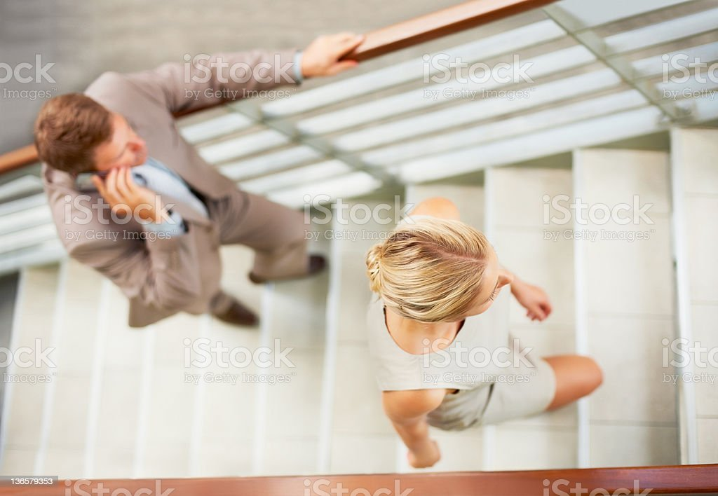 Executives climbing steps at office stock photo