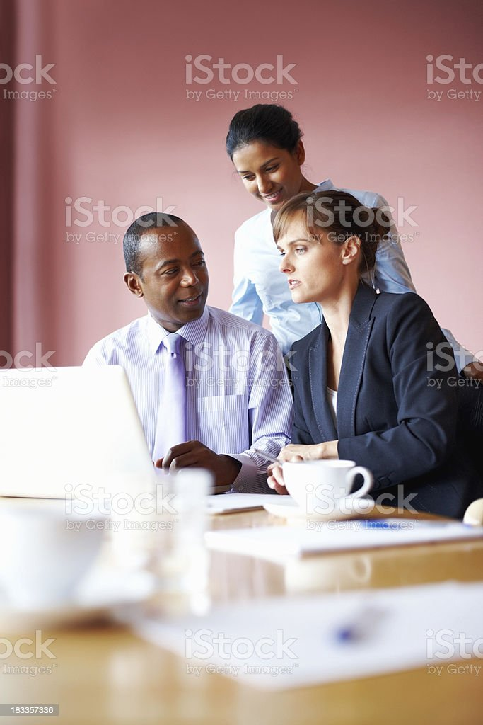 Executives in collaboration while viewing laptop royalty-free stock photo