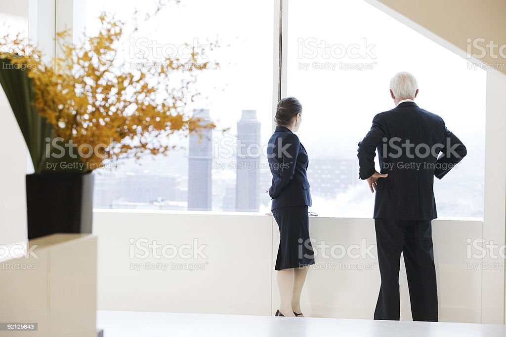 Executives looking out of office window at city view. royalty-free stock photo