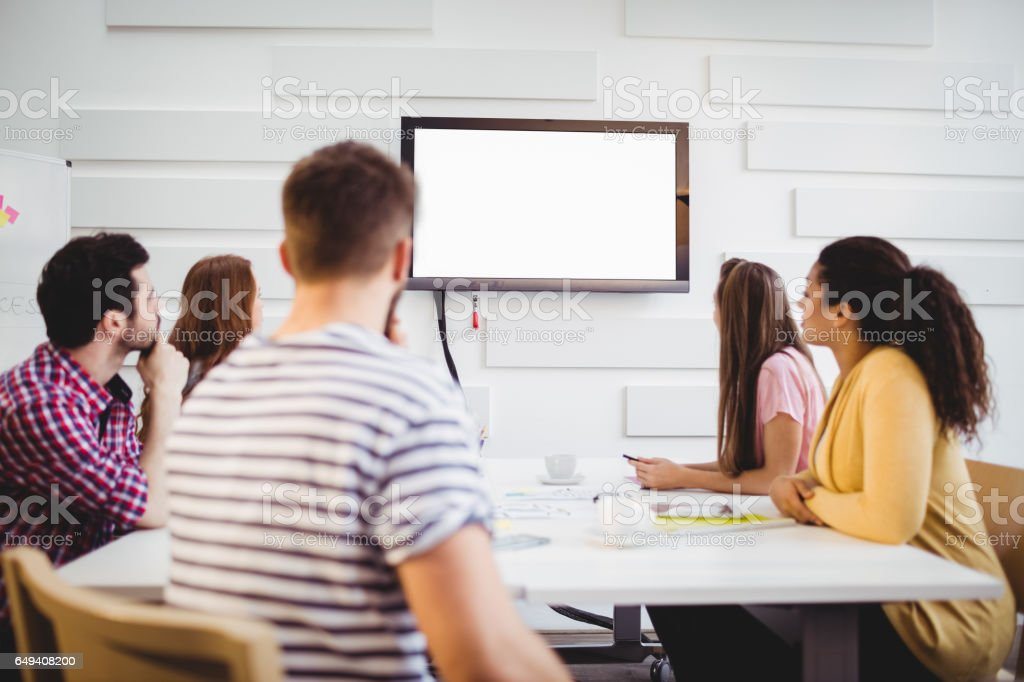 Executives watching at television during training in creative office stock photo