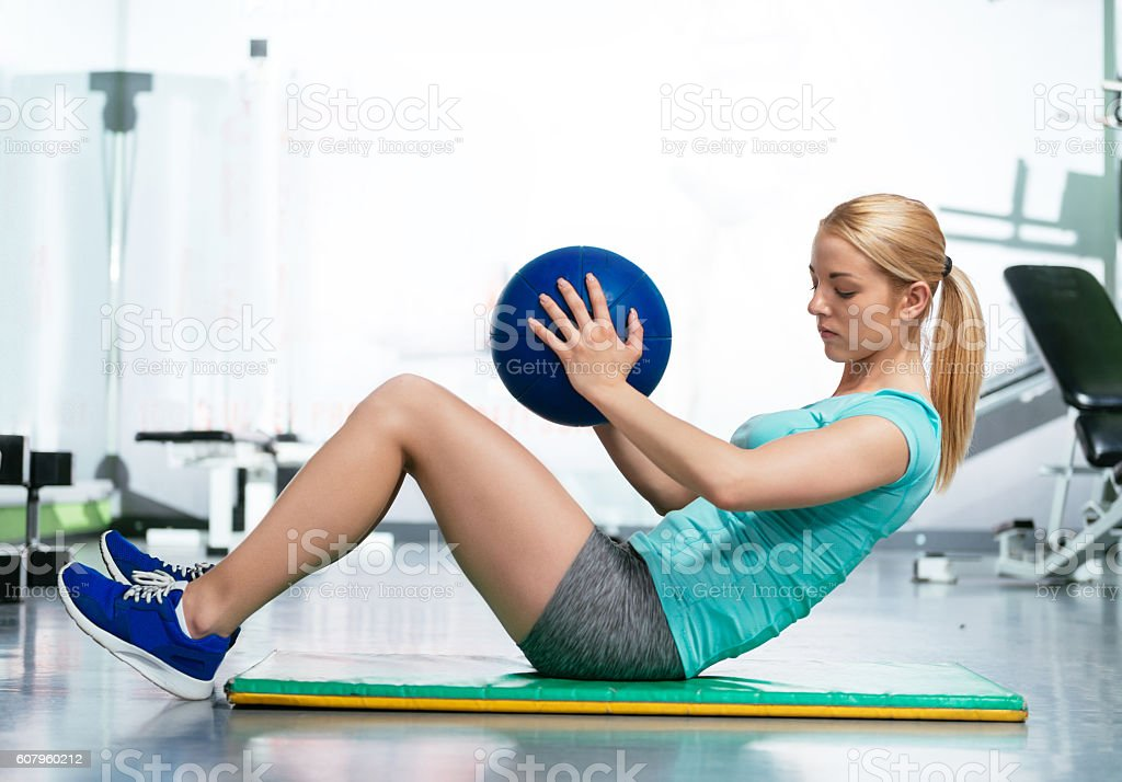 Exercise abs with medicine ball in gym stock photo