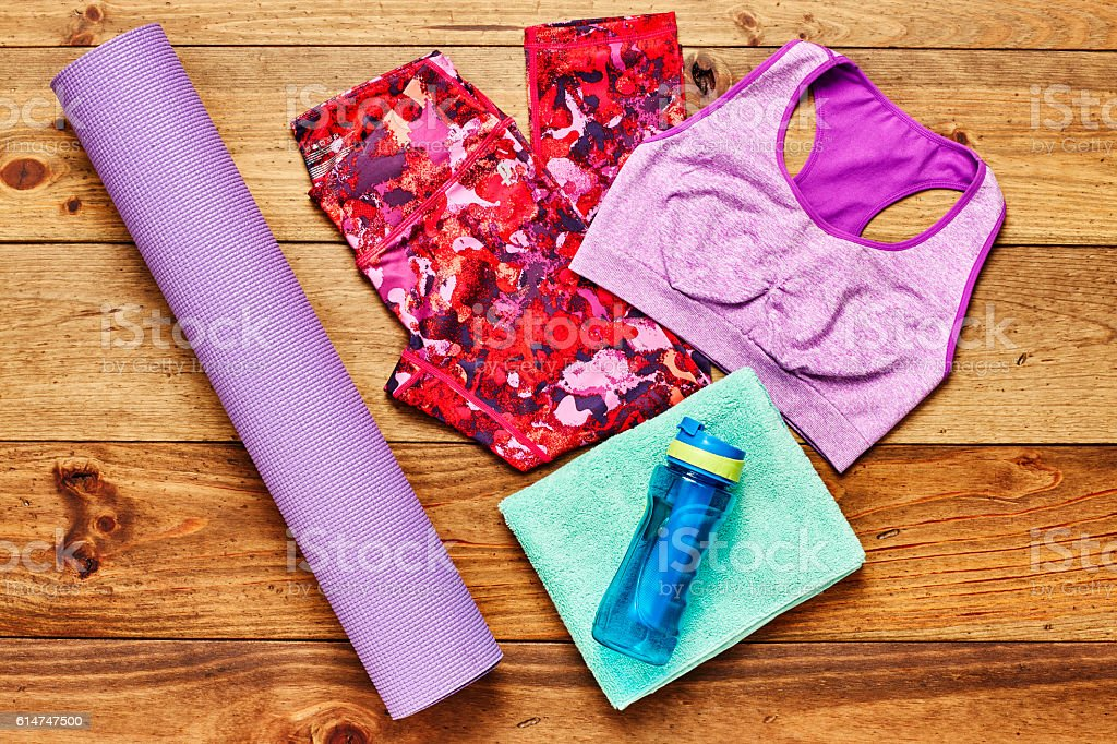 Exercise mat with sports clothing and water bottle on wood stock photo