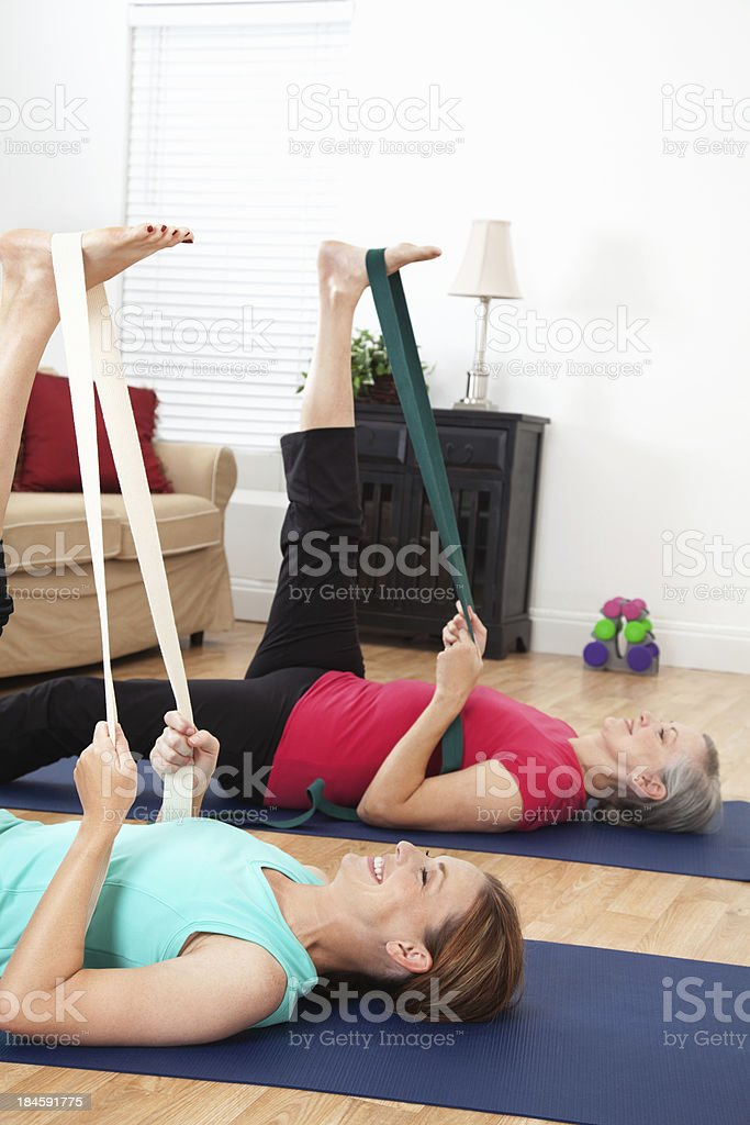 Exercise partners doing yoga strap stretching in living room stock photo