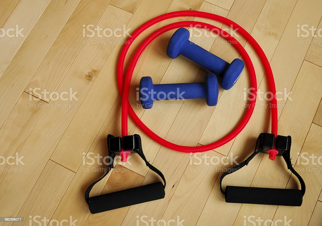 Exercise resistance bands and hand weights on wooden floor stock photo