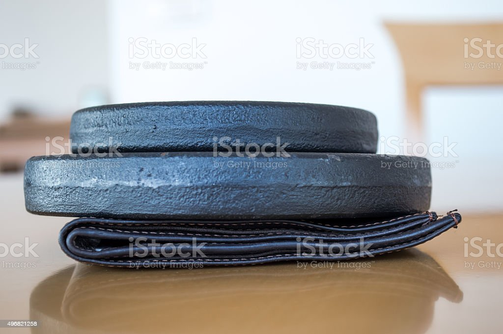 Exercise Weights/Discs Crushing/Pressing on a Wallet royalty-free stock photo