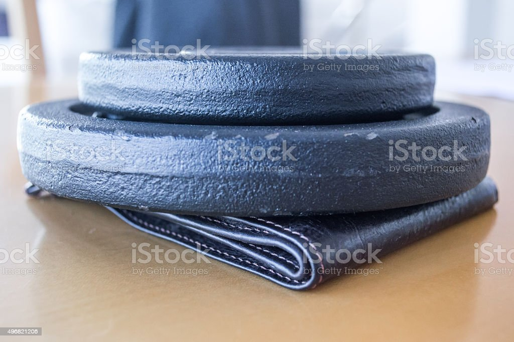 Exercise Weights/Discs Crushing/Pressing on a Wallet Side View royalty-free stock photo